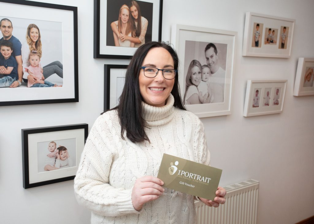 Family Portrait Photography Prize woman in cream jumper holding 1PORTRAIT STUDIO gift voucher