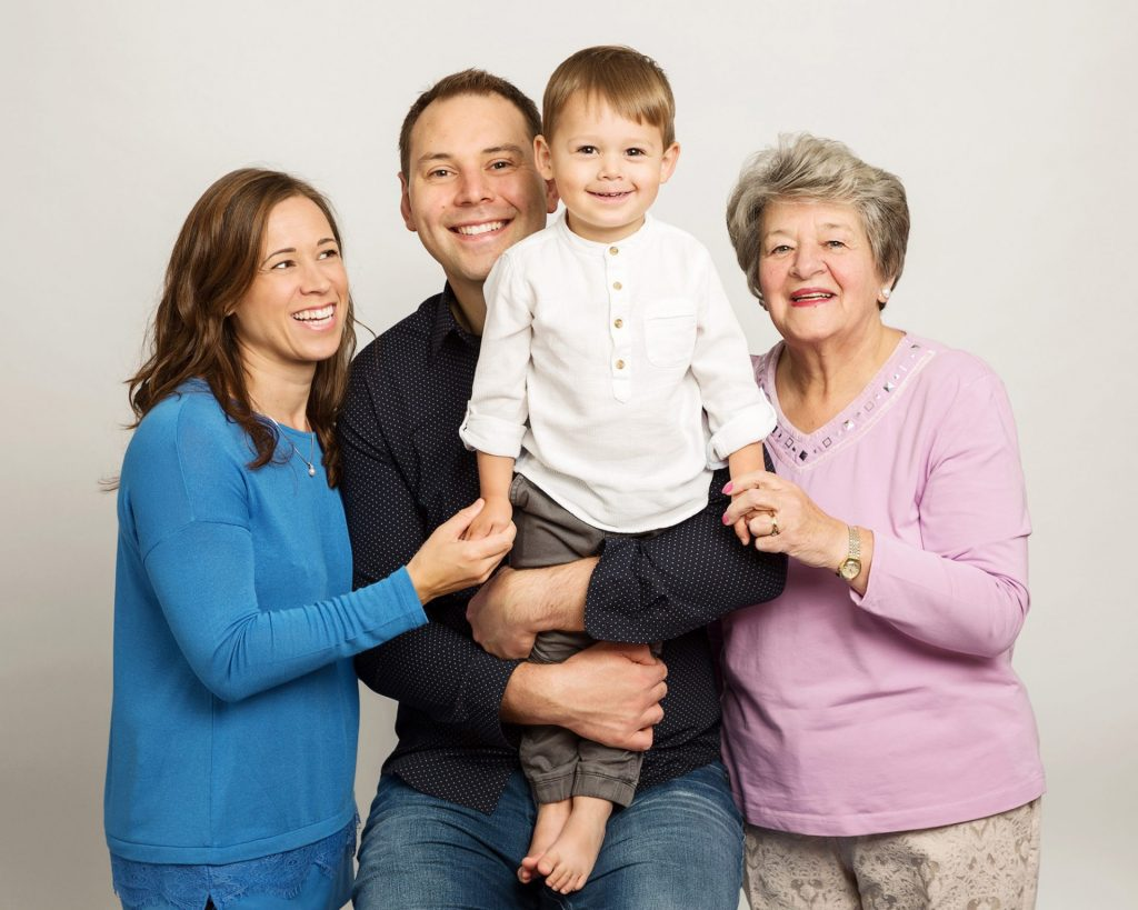 Generational portrait of grandmother, son, daughter and grandchild all smiling Family Portrait Studio