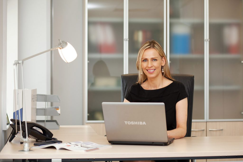 Corporate Portrait female working at laptop in office environment
