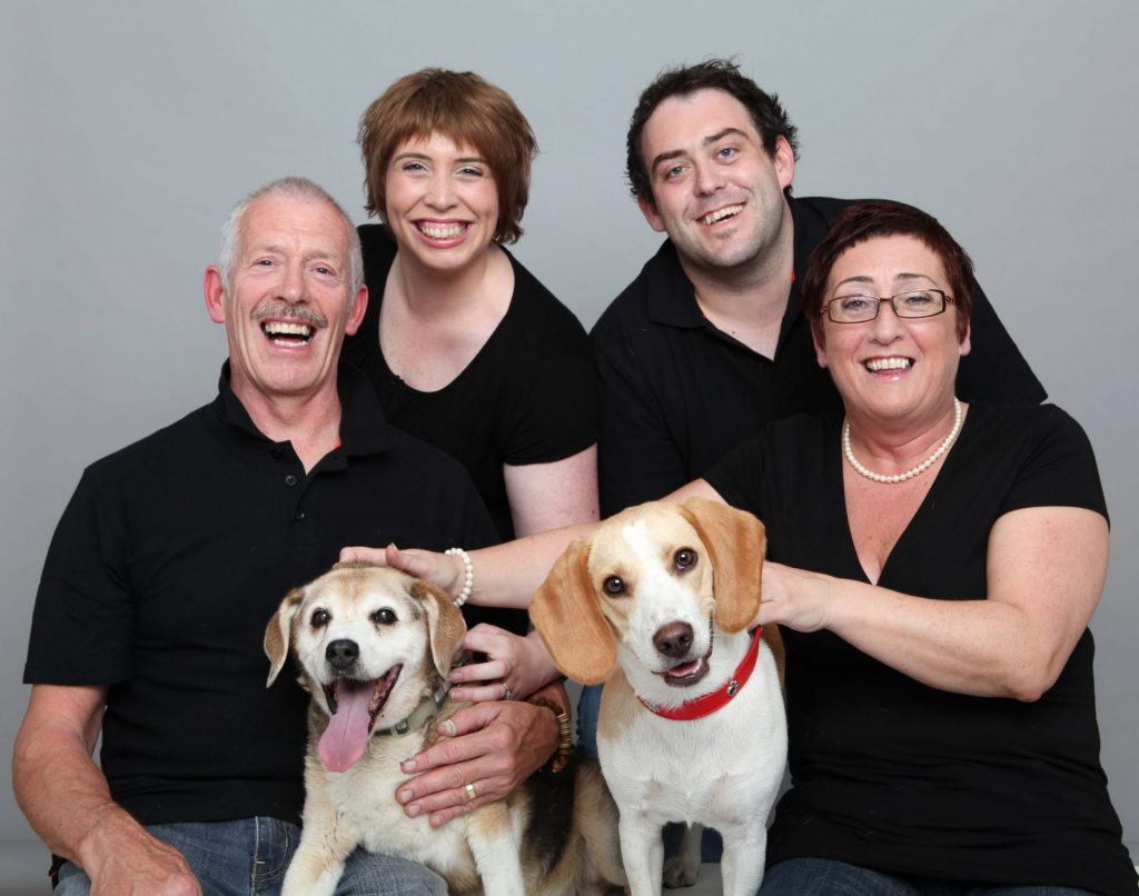 Family portrait parents and two adult children with two dogs in professional photography studio