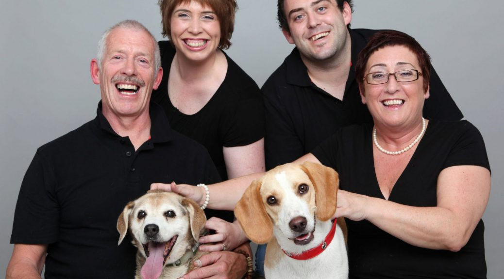 Dog & Family Photographer Family Portrait of parents and two adult children with two dogs in professional photography studio