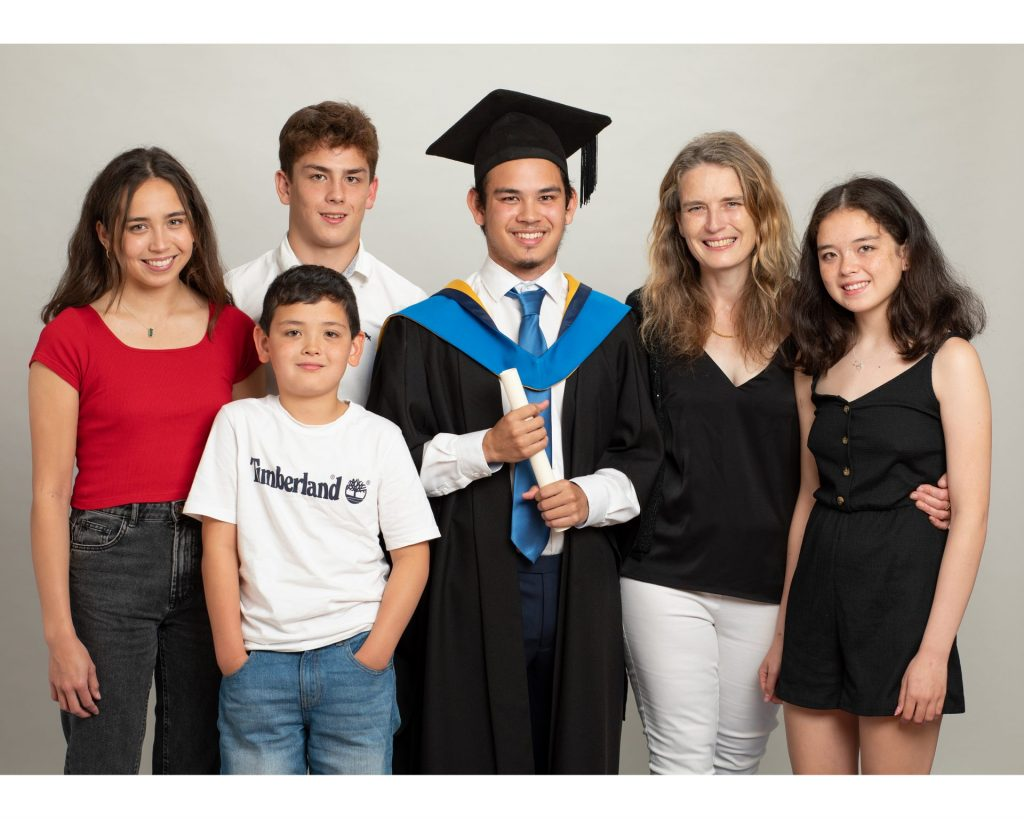 Graduation Photo for a Virtual Ceremony Portrait of a young male graduate and his family in a professional photography studio white background